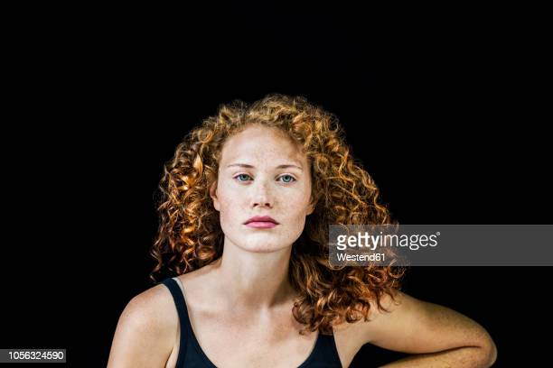 portrait of freckled young woman with curly red hair in front of black background - entschlossenheit stock-fotos und bilder