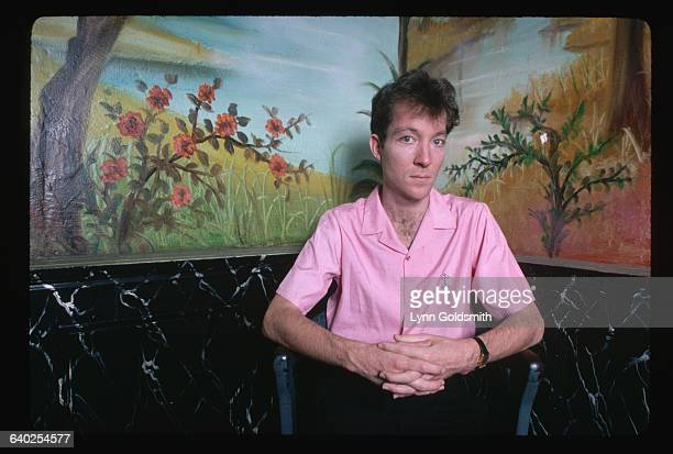 Portrait of Fred Scneider of The B-52's poses in front of a mural. He is shown waist-up, wearing a bright pink shirt.