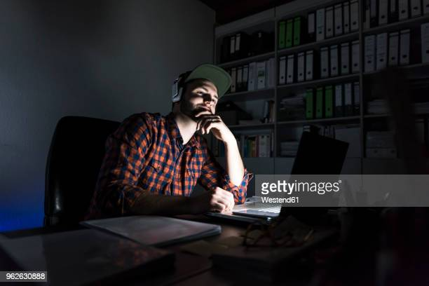 Portrait of freelancer sitting at desk at night using laptop and headphones