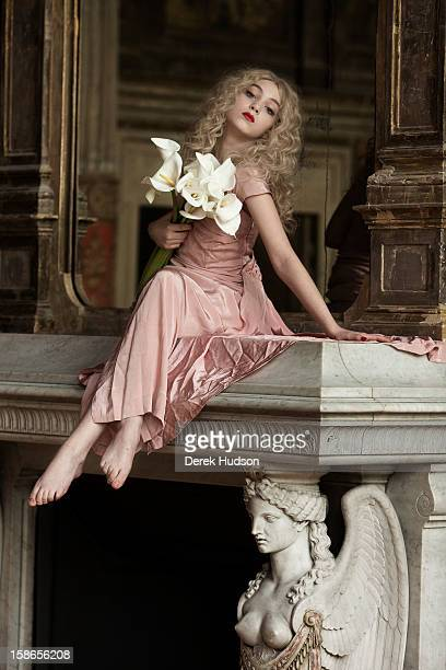 Portrait of French actress Anamaria Vartolomei sits atop a fireplace mantel and holds a bouquet of lillies bduring a photo shoot Paris France April...