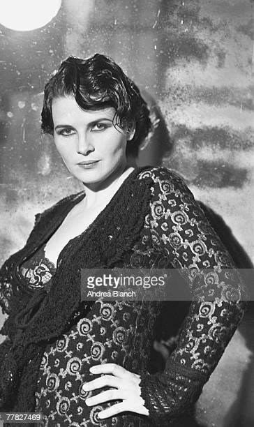 Portrait of French actress and model Juliette Binoche dressed in a brocade dress with a knit collar as she poses with a hand on her hip during a...