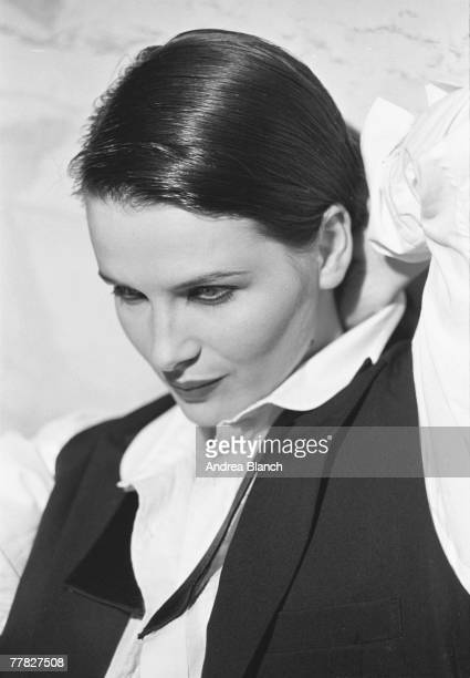 Portrait of French actress and model Juliette Binoche dressed in a short waistcoat and untied bow tie with her hair slicked down during a...