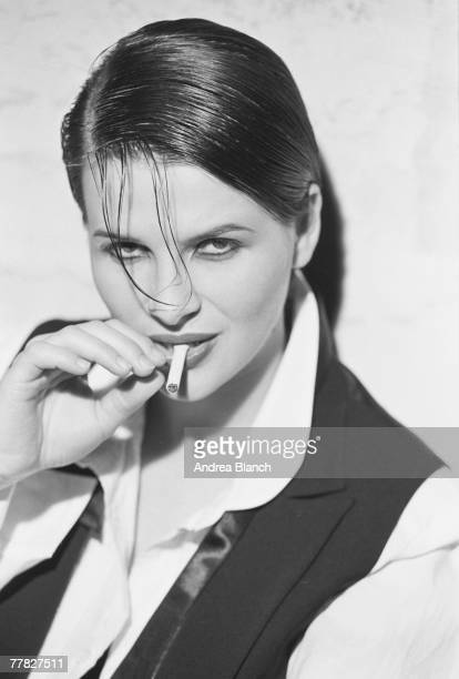 Portrait of French actress and model Juliette Binoche dressed in a short waistcoat and untied bow tie with her hair slicked down and an unlit...