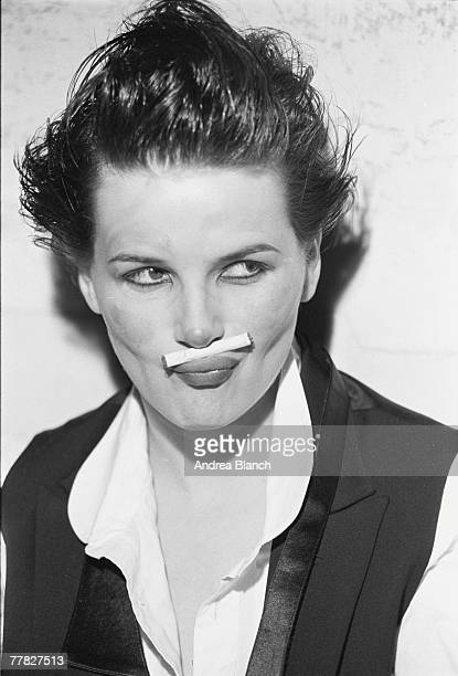 Portrait of French actress and model Juliette Binoche dressed in a short waistcoat and untied bow tie with her hair mussed up and an unlit cigarette...