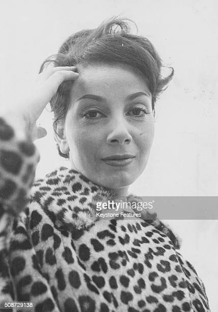 Portrait of French actress Andrea Parisy, star of the film 'Les Tricheurs', wearing a leopard print coat, circa 1959.