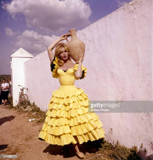 Portrait of French actress Brigitte Bardot in Spanish dress holding a jug, circa 1960s.