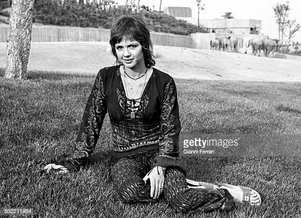 Portrait of French actress Haydee Politoff as she sits on the grass Madrid Spain 1972