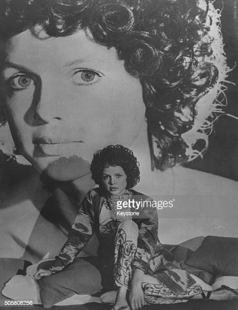 Portrait of French actress Haydee Politoff sitting in front of a large image of herself in a scene from the film 'Sweetly Atrocious' circa 1970