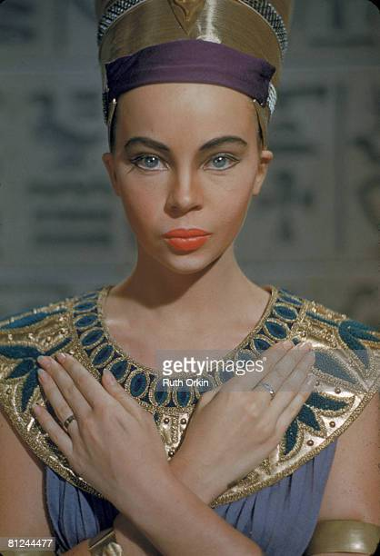 Portrait of French American actress Leslie Caron as she poses hands crossed on her chest and dressed in an 'Egyptian' costume complete with a crown...