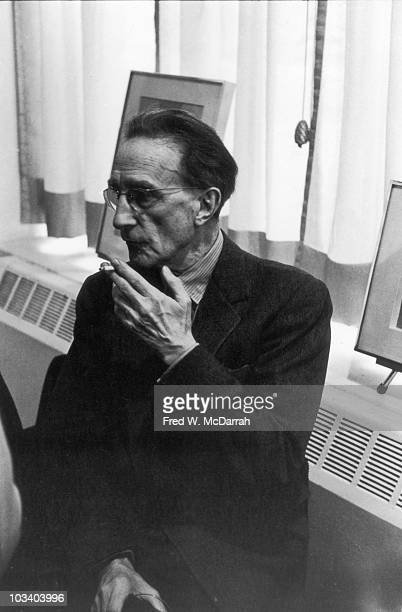 Portrait of French artist Marcel Duchamp as he smokes a cigarette in his home , New York, New York, April 30, 1963.