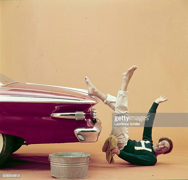 Portrait of French mime Marcel Marceau as he lies on the floor with one bare foot on the trunk of a car, New York, New York, 1961. This image was...