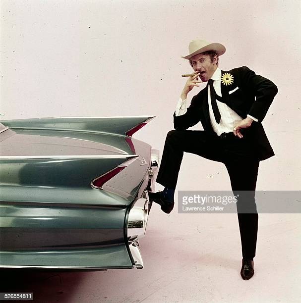 Portrait of French mime Marcel Marceau as he poses in a Stetson hat and a with a cigar, and one leg up on the bumper of a car, New York, New York,...