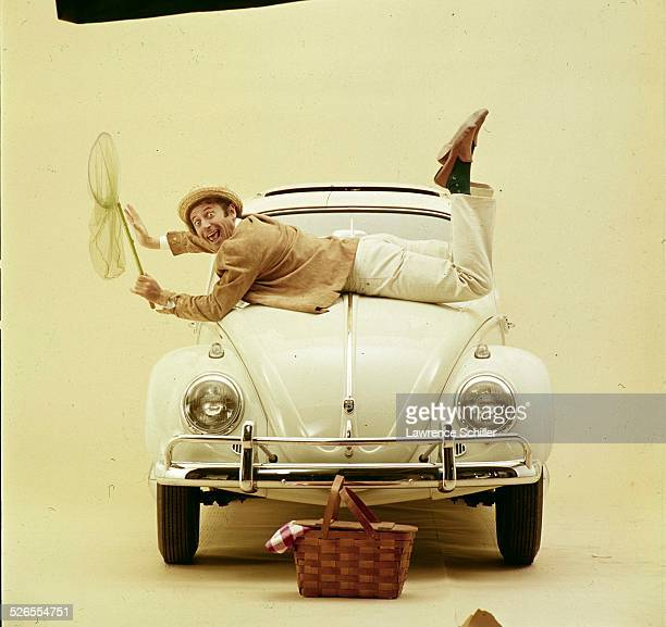 Portrait of French mime Marcel Marceau , with a butterfly net in his hands, as he lies across the hood of a Volkswagen, New York, New York, 1961....