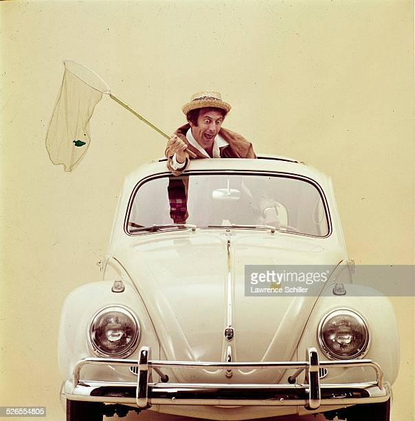 Portrait of French mime Marcel Marceau , with a butterfly net in his hand, as he poses though the sunroof of a Volkswagen, New York, New York, 1961....