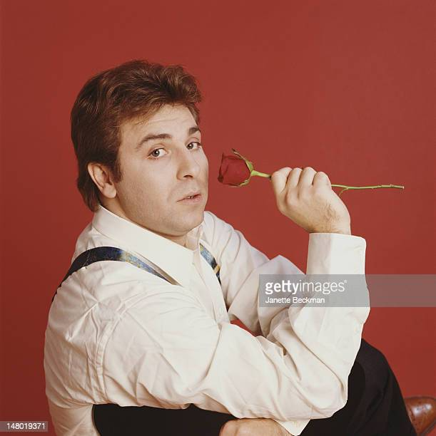 Portrait of French tenor Roberto Alagna as he poses against a red background with a rose in one hand New York New York 2006