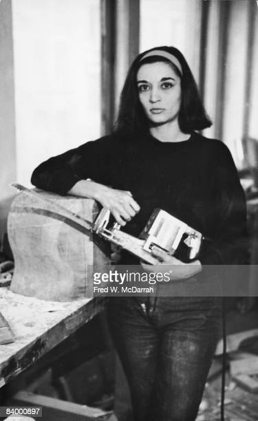 Portrait of French-born artist Marisol Escobar as she poses with an electric reciprocating saw in her hands and one elbow on a partially carved block...