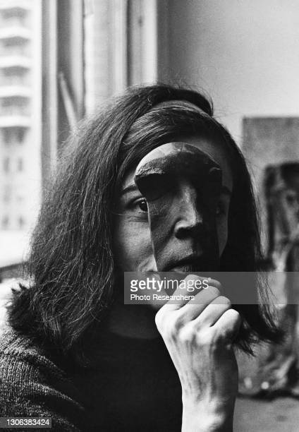 Portrait of French-born Venezuelan-American artist Marisol as she holds up a mask, obscuring a portion of her face, New York, New York, 1964.