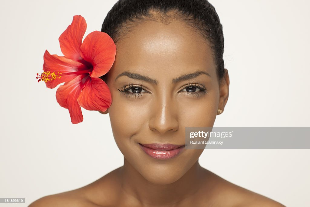 Portrait of fresh clear woman face with hibiscus flower. : Stock Photo