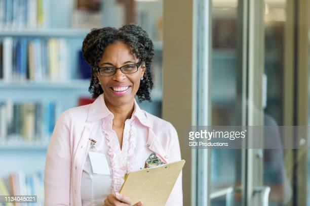 portrait of friendly school librarian - school principal stock pictures, royalty-free photos & images