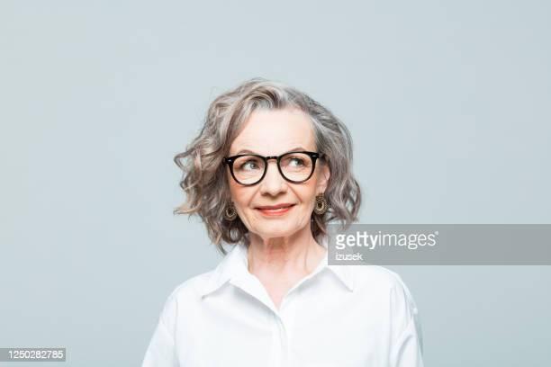 portret van vriendschappelijke hogere vrouw in wit overhemd - izusek stockfoto's en -beelden
