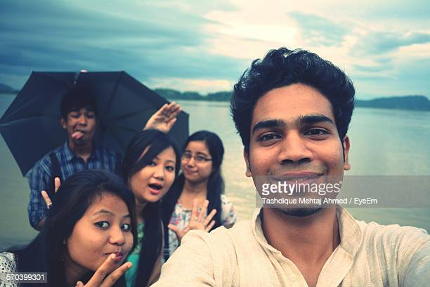portrait of friends by river against sky at dusk - guwahati stock photos and pictures