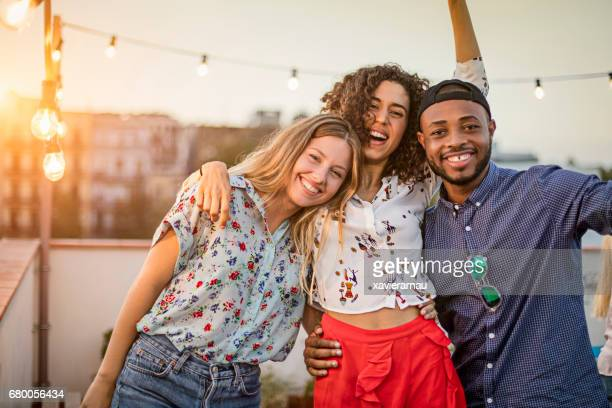 portrait of friends enjoying in terrace party - three people stock pictures, royalty-free photos & images