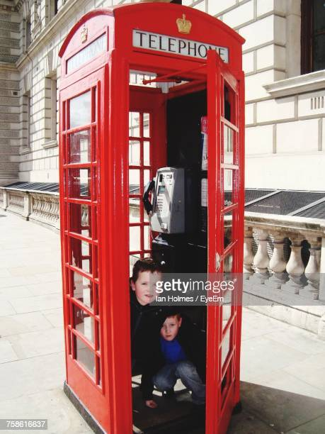 Portrait Of Friends Hiding In Telephone Booth