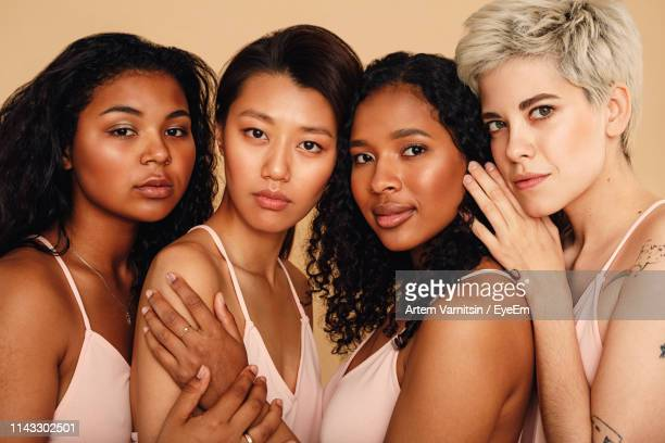 portrait of friends standing against beige background - alleen vrouwen stockfoto's en -beelden