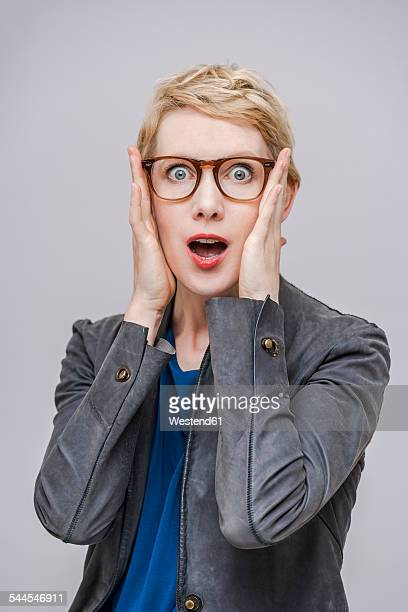 portrait of frightened blond woman with hands on her face - solo una donna di età media foto e immagini stock
