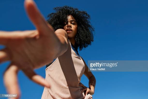 portrait of frizzy sportswoman gesturing against clear blue sky - low angle view stock pictures, royalty-free photos & images