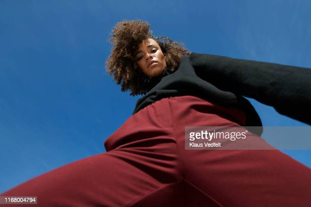 portrait of frizzy young woman against blue sky - blue pants stock pictures, royalty-free photos & images
