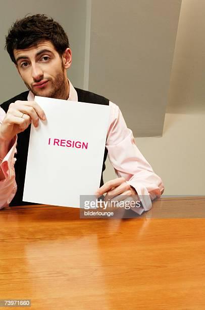 portrait of frustrated businessman sitting at desk holding resign document