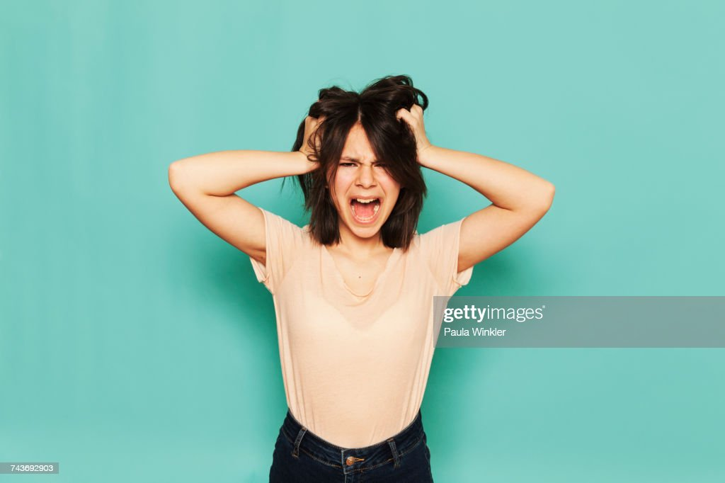 Portrait of frustrated girl shouting with hands in hair against turquoise background : Stock Photo