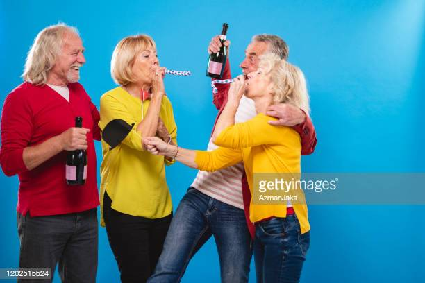 portrait of fun senior couples celebrating new year's eve - 55 59 years stock pictures, royalty-free photos & images
