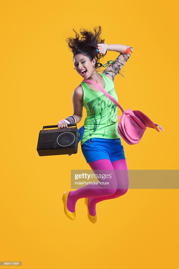 Portrait of funky woman jumping in mid air : Stock Photo