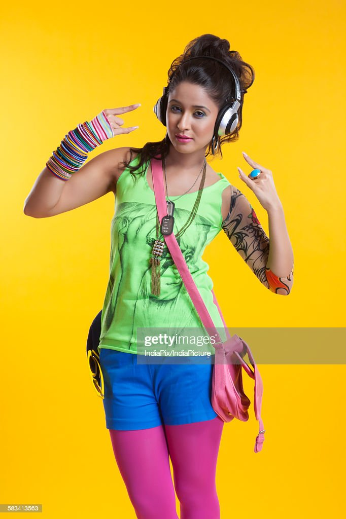 Portrait of funky young woman listening to music : Stock Photo