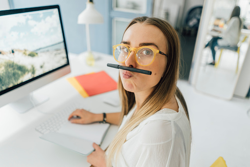Portrait of funny young woman at desk pouting mouth - gettyimageskorea