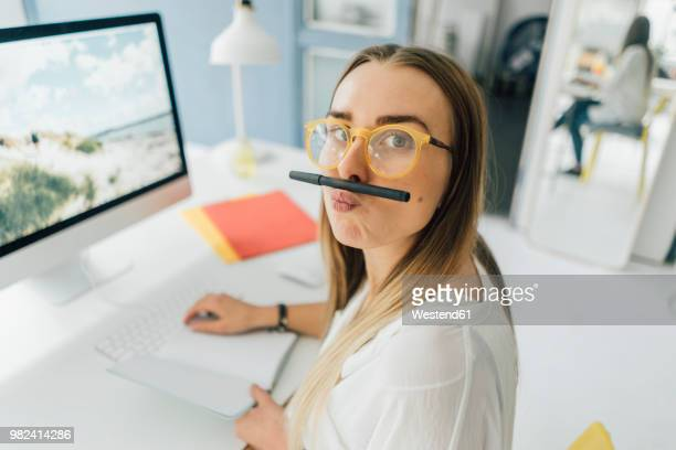 portrait of funny young woman at desk pouting mouth - spaß stock-fotos und bilder