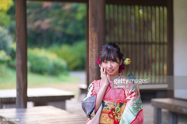 Portrait of furisode girl sitting on bench