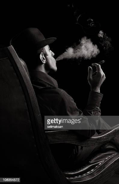 Portrait of gang member sitting on armchair and smoking cigar