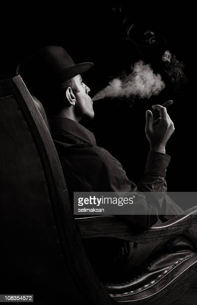 Porträt von Bandenmitglied sitzt auf Sessel und Rauchen Zigarren