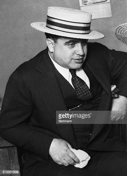 Portrait of gangster Al Capone. He is shown waist-up, wearing a straw hat. Filed 5/22/1928.