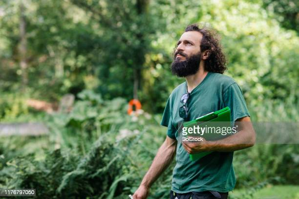 portrait of gardener with clipboard looking up - landscaped stock pictures, royalty-free photos & images