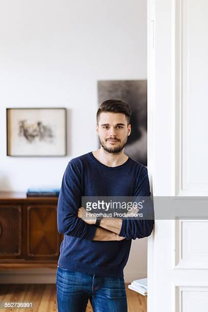 portrait of gay man in his apartment - stoppelbart stock-fotos und bilder