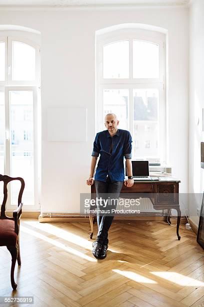 portrait of gay man leaning on desk - beautiful gay men photos et images de collection