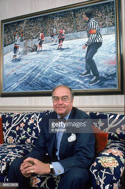 Portrait of General Manager of the New York Islanders Bill Torrey a cigar in his hand as he sits on a sofa underneath a painting that depicts Bobby...