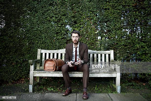 portrait of gentleman sitting on bench with tablet computer - panchina foto e immagini stock