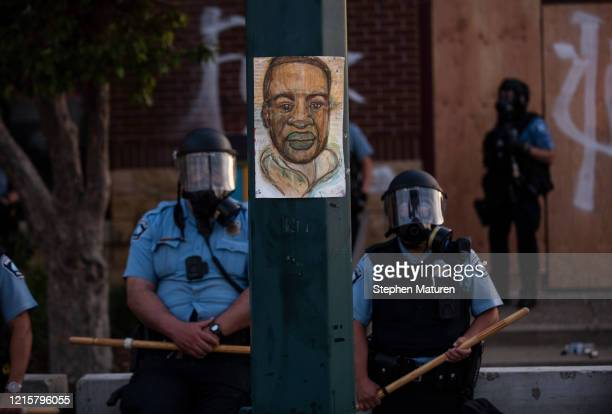 A portrait of George Floyd hangs on a street light pole as police officers stand guard at the Third Police Precinct during a face off with a group of...