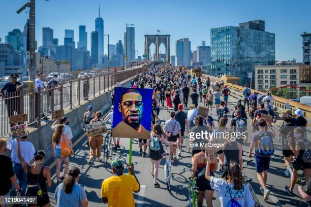 Portrait of George Floyd held by participants taking the Manhattan inbound roadway at the march across the Brooklyn Bridge. Thousands of New Yorkers...