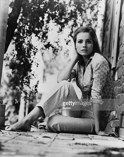 Portrait of German actress Eva Renzi star of the film 'The Jolly Pink Jungle' sitting on the floor outdoors February 19th 1968